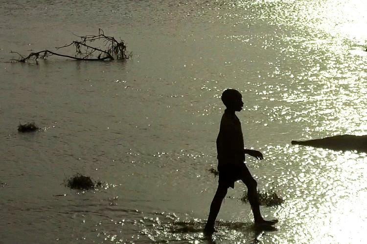 A Kenyan boy walking through a sunlit river
