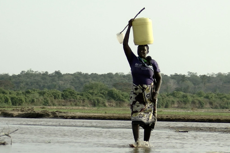 A Kenyan woman carrying 20 litres of water on her head